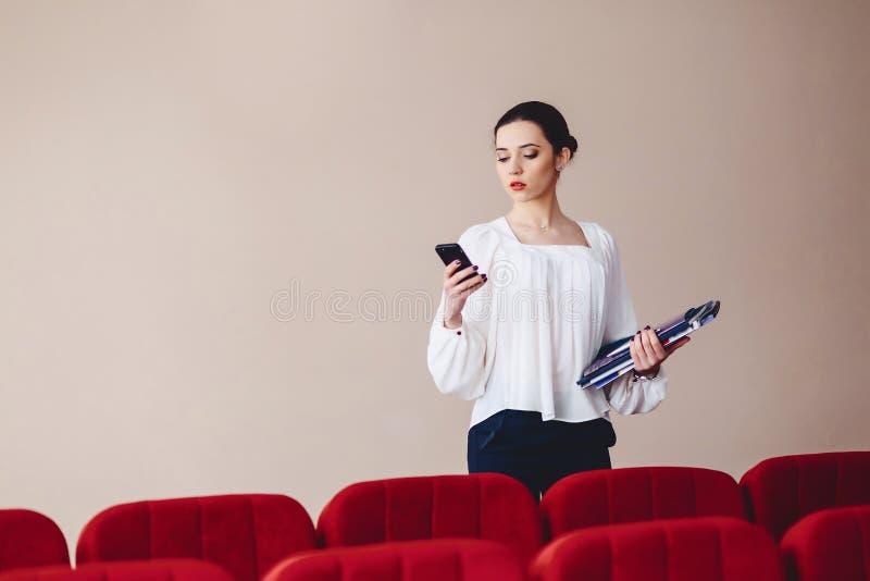 Messaging för affärskvinna på telefonen med dokument i hennes händer royaltyfri bild