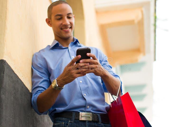 Messaging för afrikansk amerikanmantext på telefonen med shoppingpåsar royaltyfria bilder