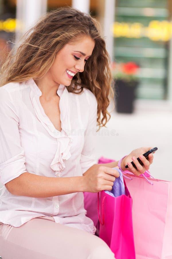 Messaging för shoppingkvinnatext fotografering för bildbyråer