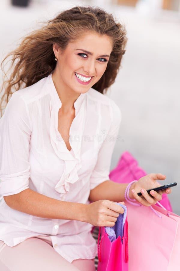 Messaging för shoppingkvinnatext royaltyfri fotografi