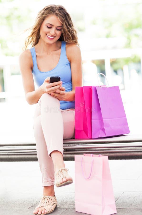 Messaging för shoppingkvinnatext royaltyfri bild