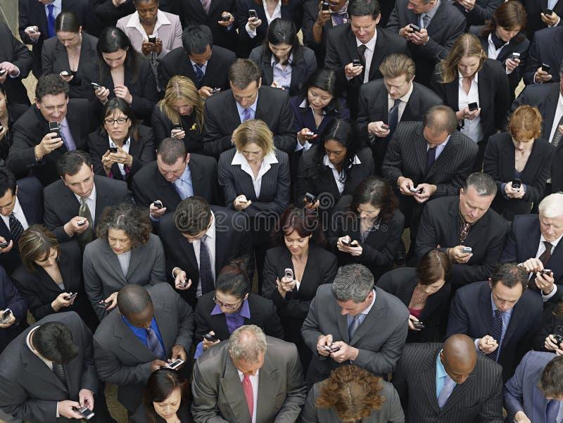 Messaging för text för affärsgrupp med mobiltelefoner royaltyfria foton