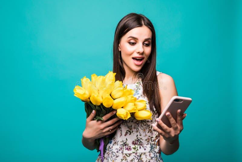 Messege van de mens Portret van een verrast jong meisje die in kleding mobiele telefoon bekijken terwijl het houden van groot boe royalty-vrije stock fotografie