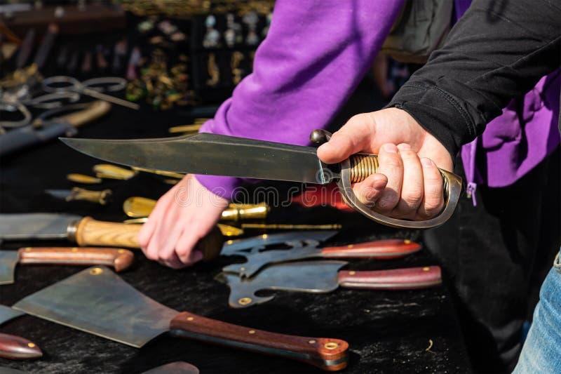 Messen breed blad met geribbeld handvat op een achtergrond van van de het close-up in hand mens van de wapensbijl het ontwerpwape royalty-vrije stock afbeelding