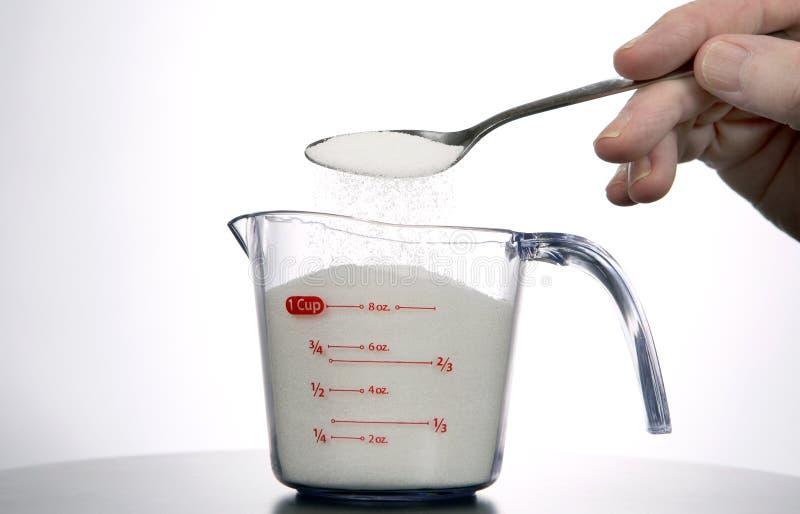 Messen einer Schale Zuckers stockbild