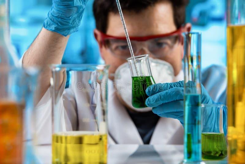 Messende Probe des Chemikers von Flüssigkeiten im Forschungslabor stockbild