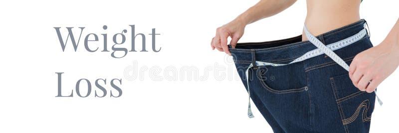 Messende Taille des Gewichtsverlusttextes und der Sitzfrau mit übergroßer Hose lizenzfreie stockfotos