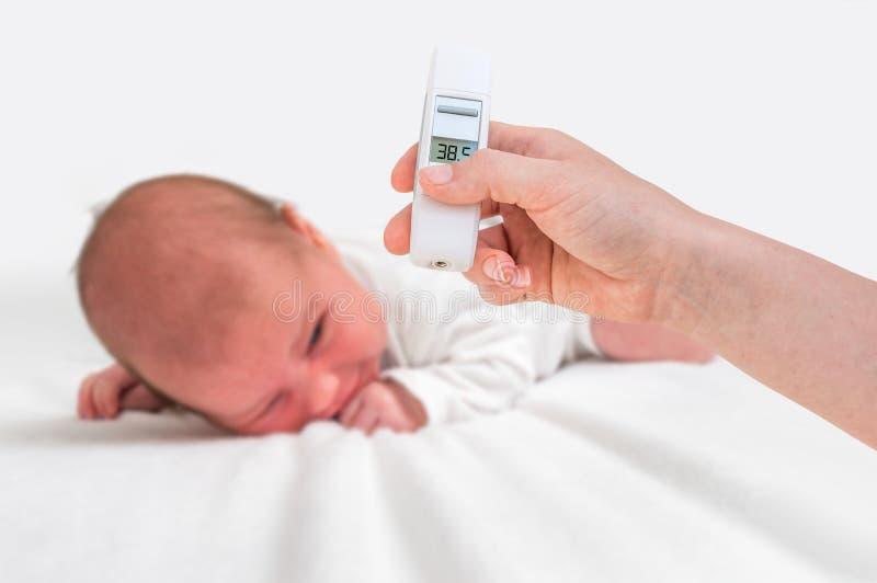 Messende Temperatur zu einem neugeborenen Baby mit digitalem Thermometer lizenzfreie stockfotos