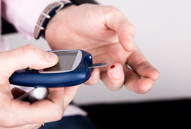 Messende waagerecht ausgerichtete Blutprobe der Glukose unter Verwendung des ultra Mini-glucometer und kleiner Blutstropfen von d stockfotos