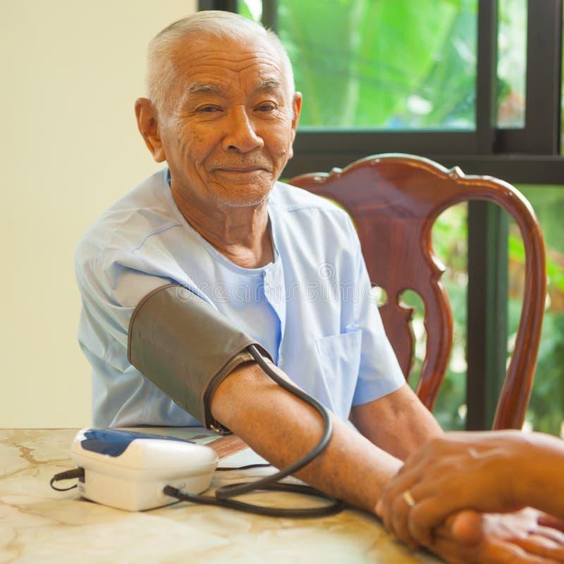 Messender Blutdruck Doktors des männlichen Patienten lizenzfreies stockbild