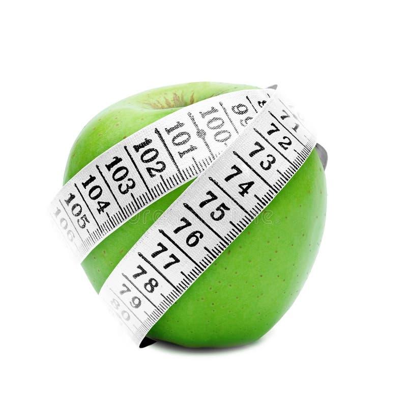 Messendes Band um grünen Apfel stockfotografie