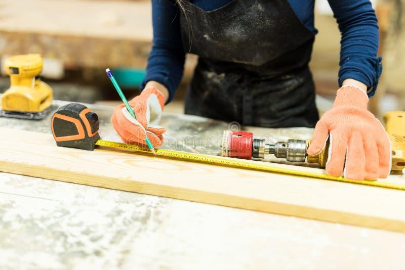 Messendes Holz des weiblichen Tischlers stockfoto
