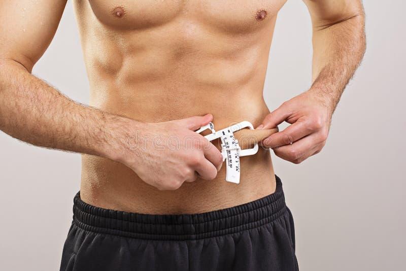 Messendes Körperfett des geeigneten Sportlers mit Tasterzirkel lizenzfreie stockfotos