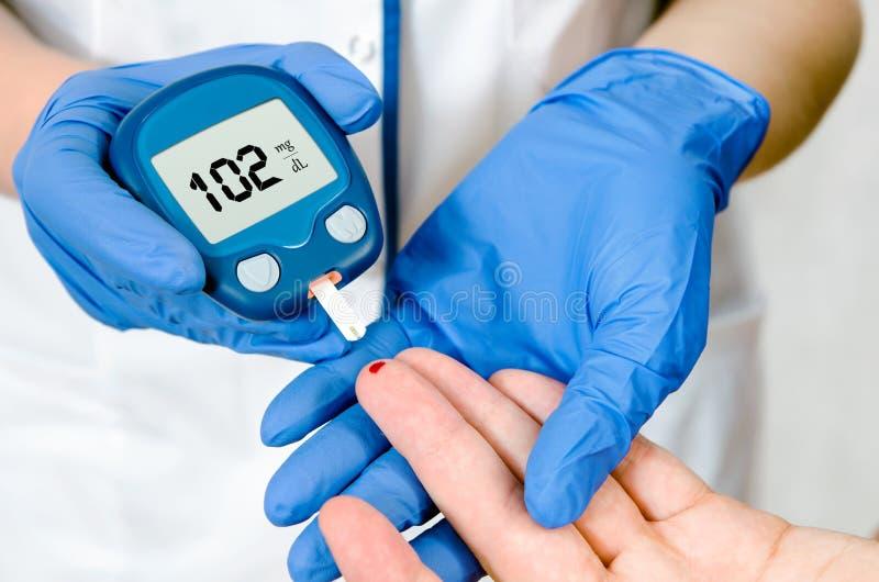 Messendes waagerecht ausgerichtetes Blut der Glukose Doktorfrau lizenzfreie stockfotos
