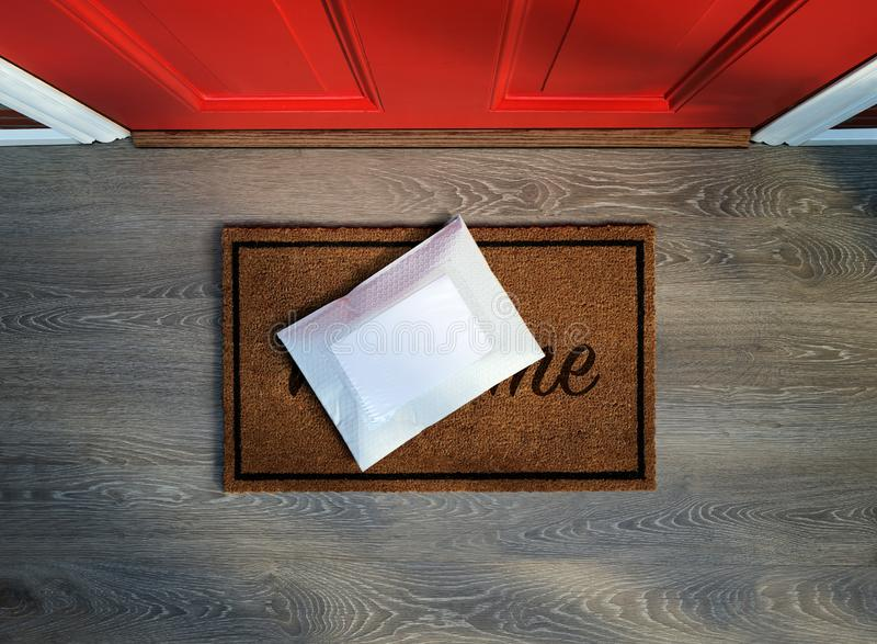 Messenger envelope pack delivered outside front door. Messenger envelope pack delivered to door step. Overhead view. Copy space stock image