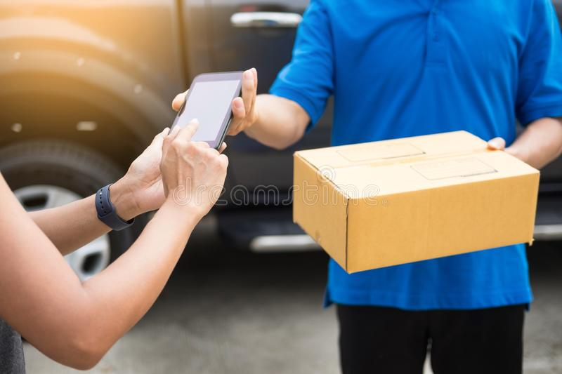 messenger man hold box and talk on smart phone and payment terminal in hands, Package delivery concept. royalty free stock photography