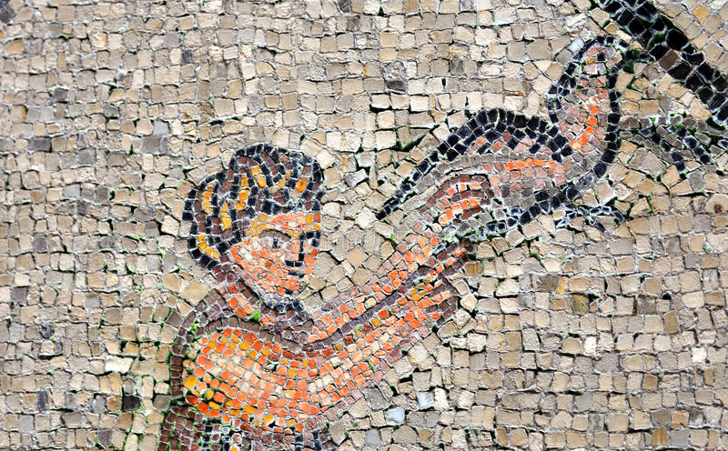 Messenger service. A man holds up a messenger pigeon for release to carry a message in an ancient roman mosaic part of the UNESCO listed floor of the basilica of stock photos