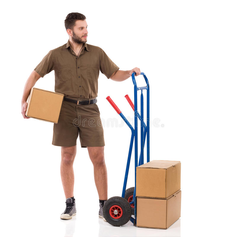 Messenger Is Standing Close To Push Cart And Looking Away. Messenger is standing close to push cart, holding package under his arm and looking away. Full length stock photography