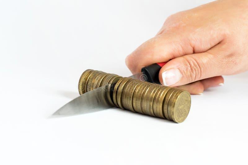 Messer, das einen Stapel der Münze schneidet lizenzfreie stockfotografie