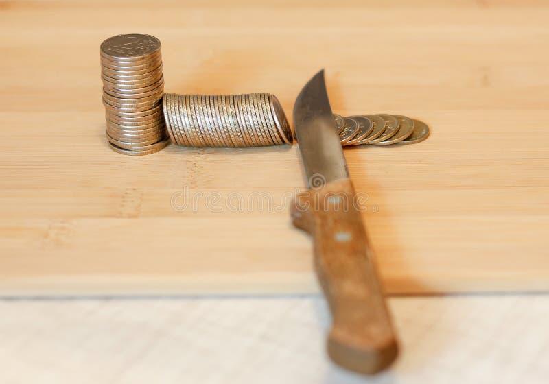 Messer, das einen Stapel der Münze schneidet Konzept von Etatverkürzungen, Einsparungen, r lizenzfreie stockfotografie