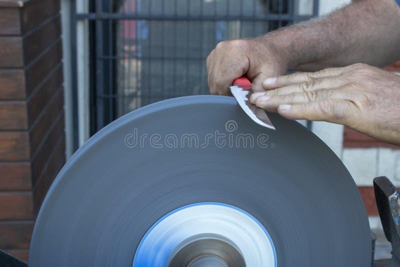 Messer, das Hand schärft und Maschinennahaufnahme versandet stockfotografie
