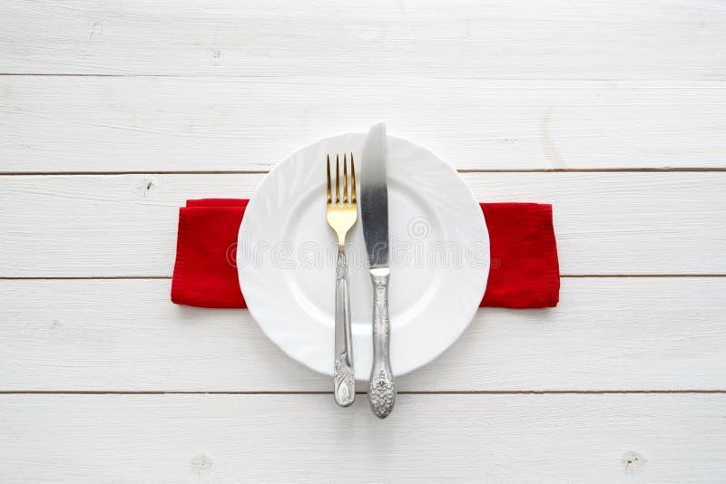 Messer, Gabel und Teller über Holztisch stockfoto