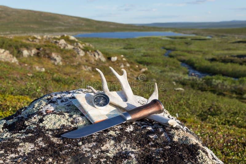 Messer, Kompass und Karte auf dem Felsen stockbild