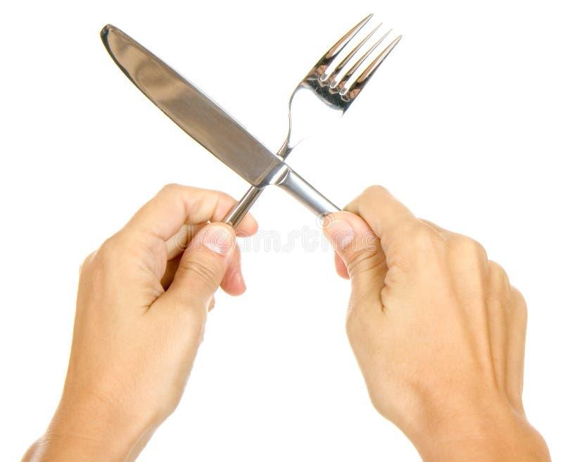 Messer und Gabel in den Händen stockfotografie