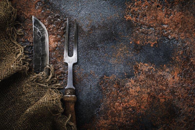 Messer und Gabel für Fleisch auf rostiger Tabelle lizenzfreies stockbild