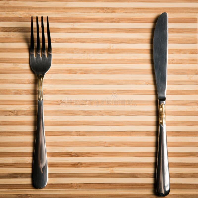 Messer und Gabel stellten auf ein hölzernes Brett ein Freier Raum für Männer eines Restaurants stockfoto
