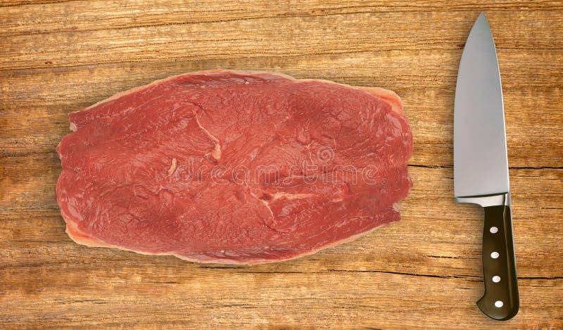 Messer und ungekochtes Fleisch auf Schneidebrett auf Weiß stockfotografie