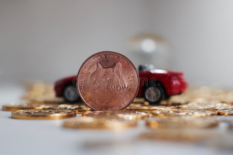 Messing-dogecoin Münze nahe rotem Auto lizenzfreie stockfotografie