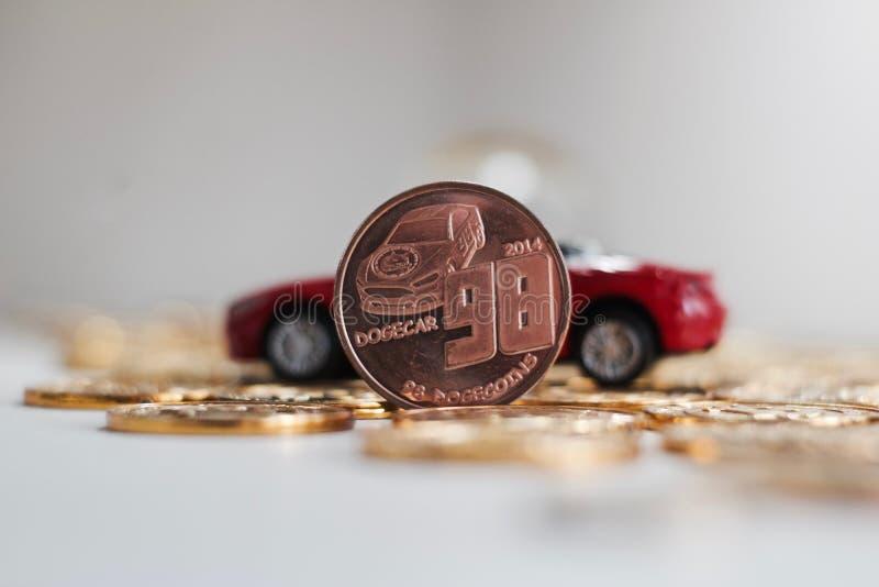 Messing-dogecoin Münze nahe rotem Auto stockfoto