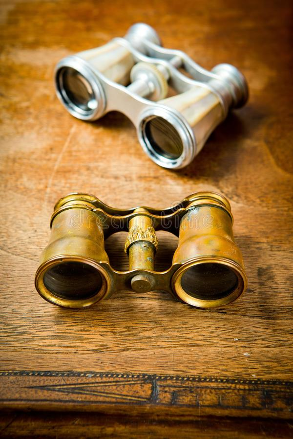 Messing- und silberne Ferngläser der Weinlese auf altem Holztisch stockfotos