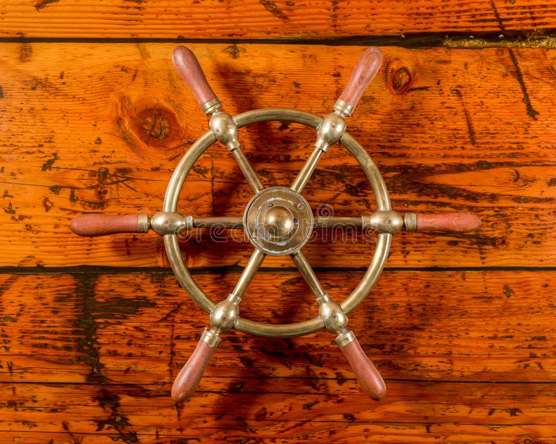 Messingschiffs-Rad auf strukturiertem Holz lizenzfreie stockbilder