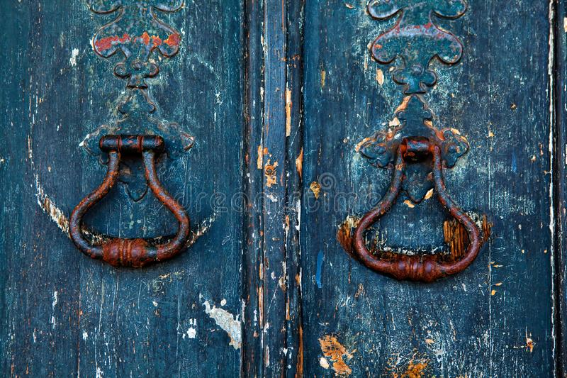 Messingskloppers op oude houten deur stock afbeelding
