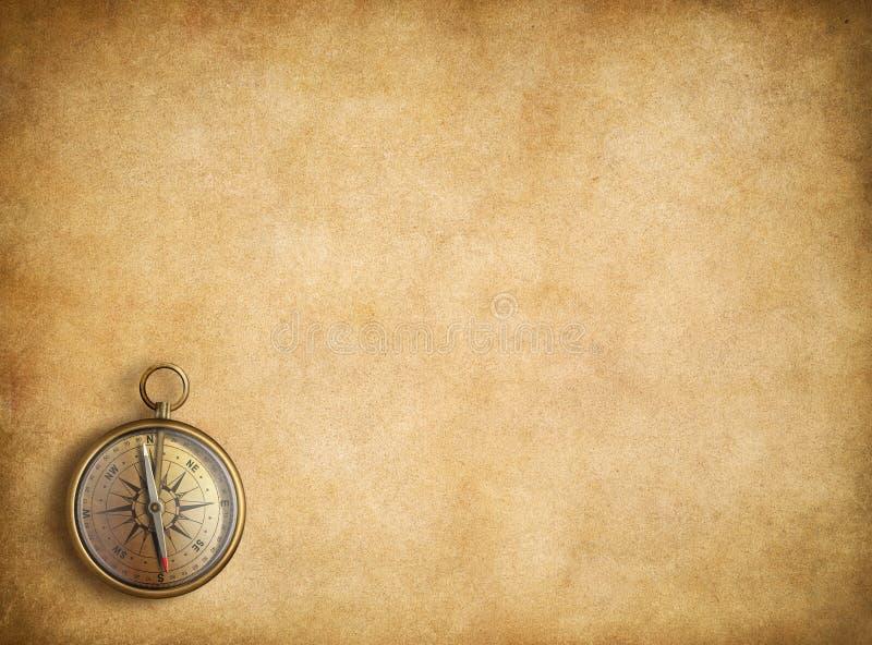 Messingskompas op lege uitstekende document achtergrond stock foto