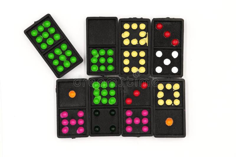 Messo dei domino, la bugia di domino sopra, chiude sui vecchi domino neri di colore con i pezzi variopinti del punto isolati su f immagine stock