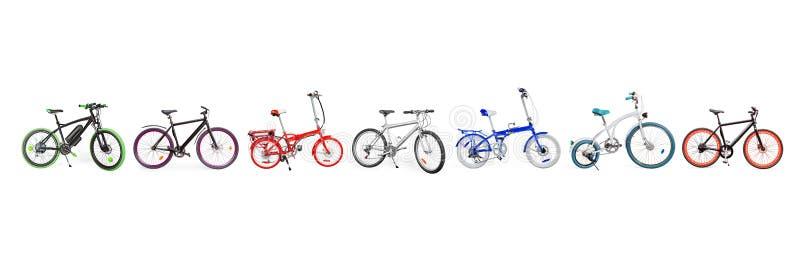 Messo di elettrico, di urbano, l'incrociatore, MTB e le bici pieganti disposti nella singola linea isolata con il percorso di rit fotografie stock libere da diritti