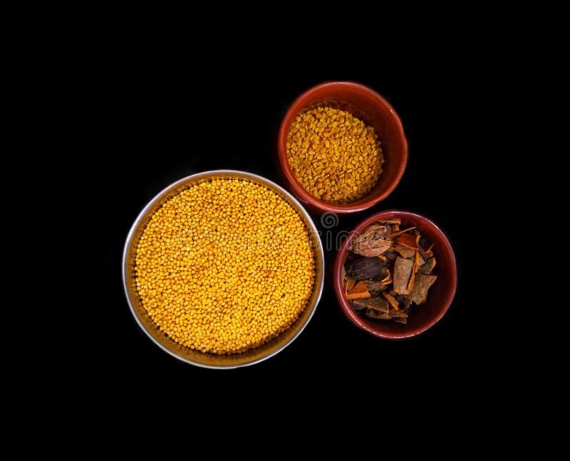 Messo di tre tipi di spezie e di erbe in una ciotola isolata su un fondo nero fotografia stock libera da diritti