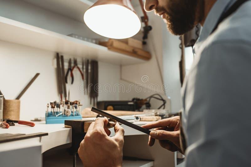 Messo a fuoco su un processo Chiuda su di giovane gioielliere maschio che lavora e che modella un anello non finito con uno strum fotografie stock libere da diritti