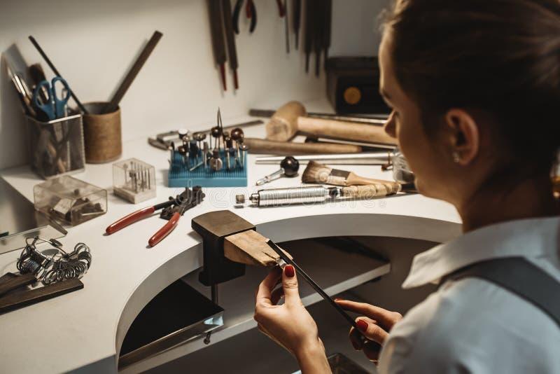 Messo a fuoco su un processo Punto di vista posteriore di un gioielliere femminile che lavora e che modella un anello non finito  fotografia stock