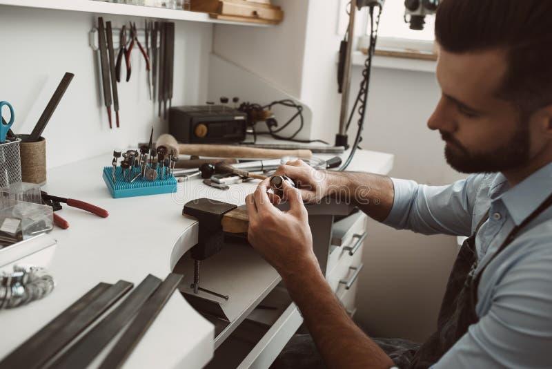 Messo a fuoco sul suo lavoro Foto del primo piano del gioielliere maschio che fa un nuovo anello d'argento al suo banco da lavoro fotografie stock libere da diritti