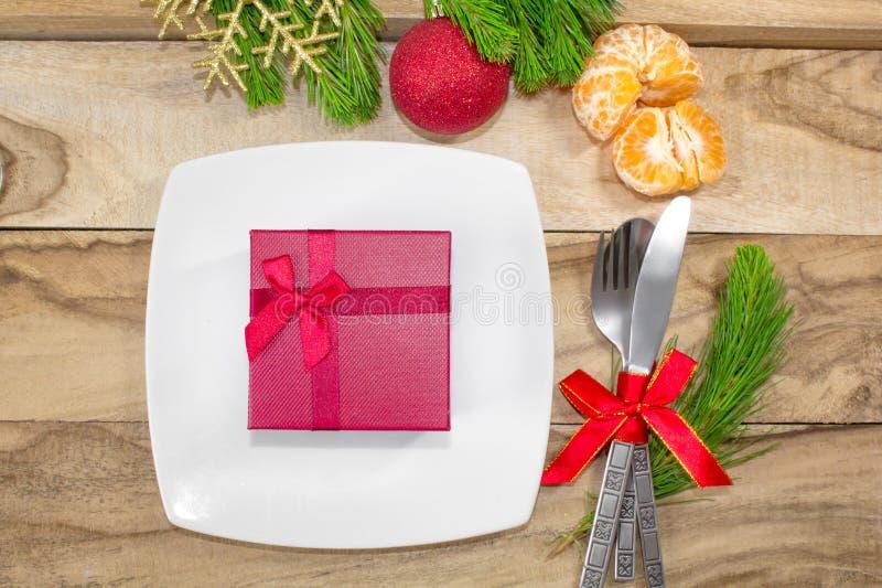 Messo per le tavole di Natale, i mandarini, le decorazioni, l'abete e un piatto con un regalo e una coltelleria Priorità bassa fe immagine stock libera da diritti