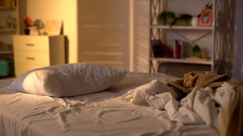 Messy bed, white pillow with blanket lying on bed unmade, oversleeping concept royalty free stock photo