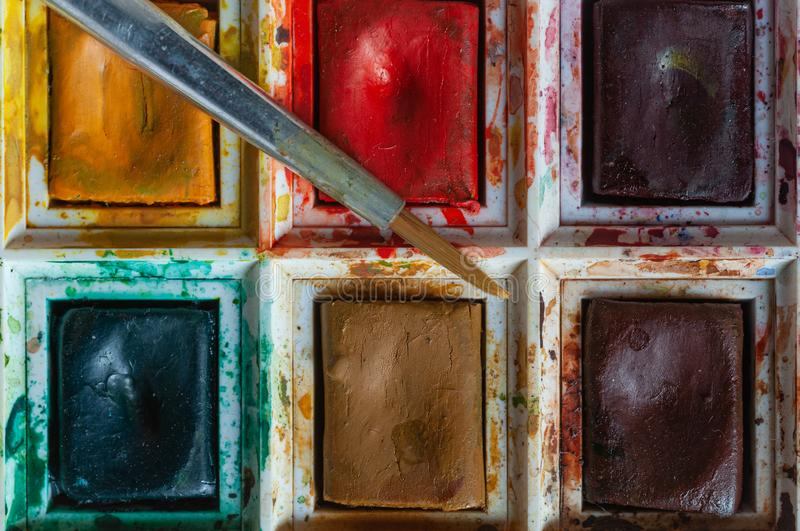 Messy box of watercolour paints and brush stock images