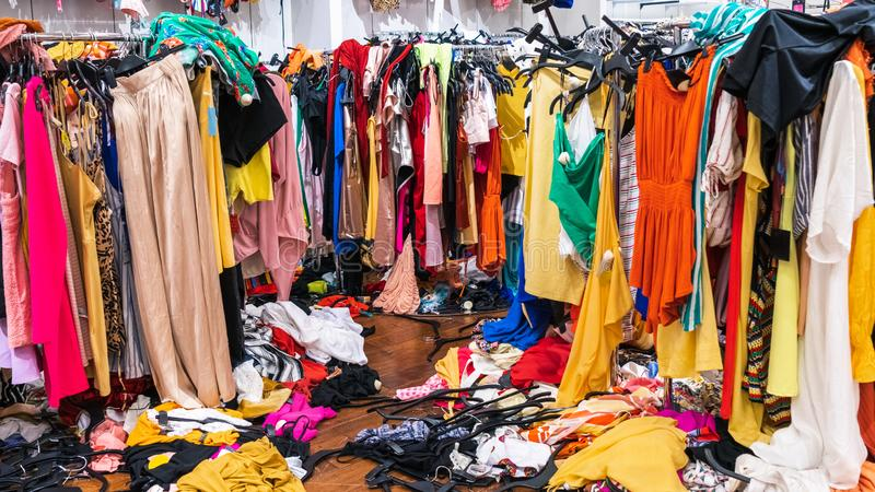 Messy clearance section in a clothing store, with colorful garments on racks and on the floor stock photography