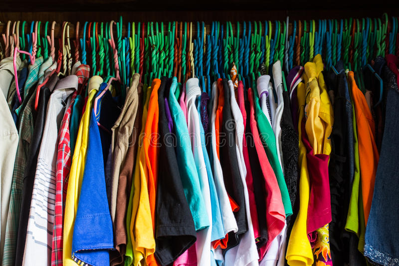 Messy closet overfilled with colorful woman clothes on hangers. And stuffed in any available space royalty free stock photography