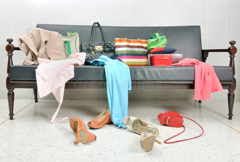 Messy clothes, lady bag and shoes scattered on a sofa. Messy clothes, lady bag and shoes scattered on a leather sofa stock image