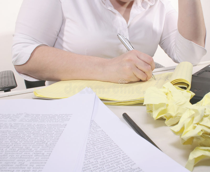 Messy Desk. A woman in a white button-down shirt writing on a sheet of paper, surrounded by discarded papers, research materials and a computer royalty free stock photography